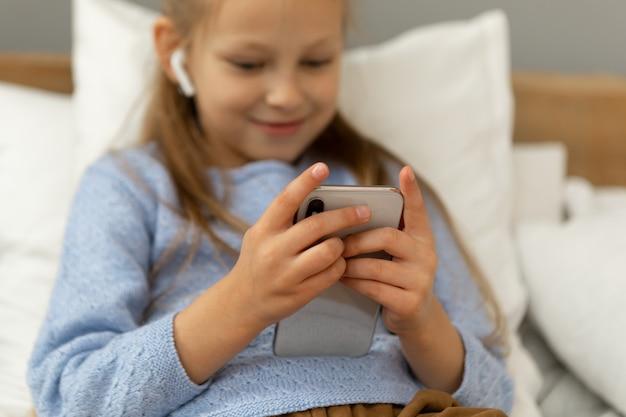소녀는 그녀의 손에 전화를 들고 화면을보고 웃고