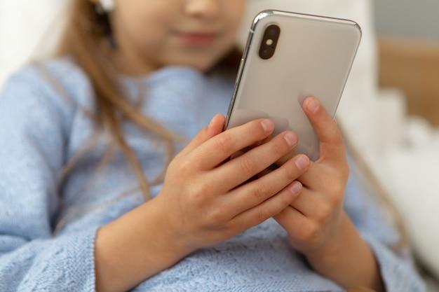 Девушка держит телефон в руках крупным планом