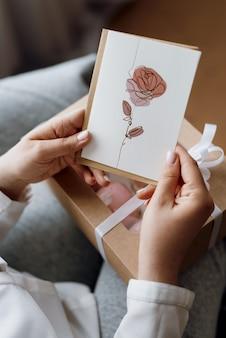 花が描かれたはがきを持っている女の子