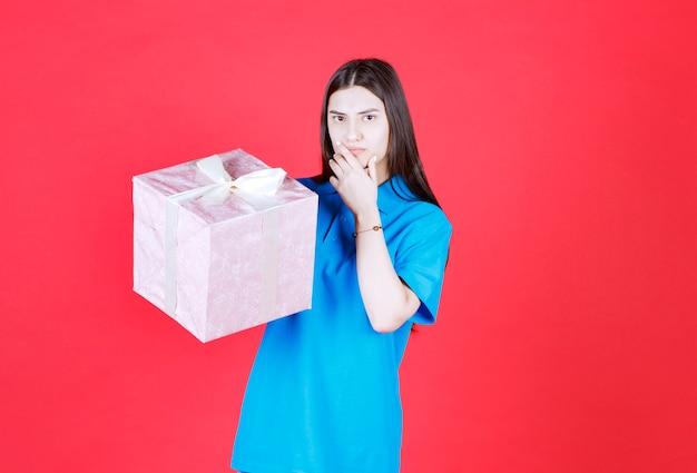 Девушка держит фиолетовую подарочную коробку и выглядит смущенной и задумчивой