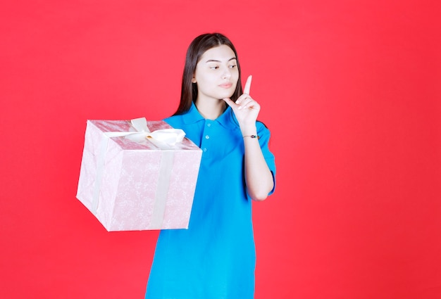 Девушка держит фиолетовую подарочную коробку, обернутую белой лентой, и выглядит смущенной и задумчивой.