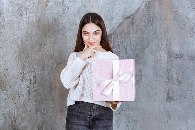 Девушка держит фиолетовую подарочную коробку, обернутую белой лентой, и выглядит задумчивой или у нее есть хорошая идея.