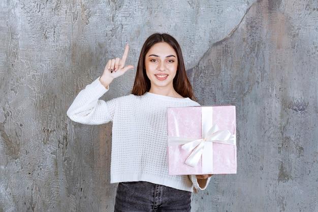 白いリボンで包まれた紫色のギフトボックスを持っている女の子は、思慮深く見えるか、良い考えを持っています。