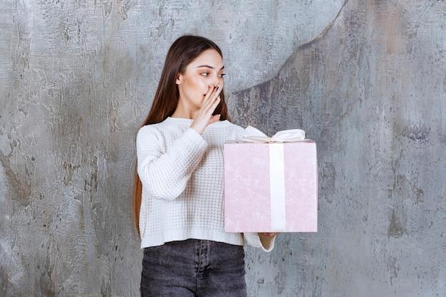 Девушка держит фиолетовую подарочную коробку, обернутую белой лентой и говорит что-то секретное.