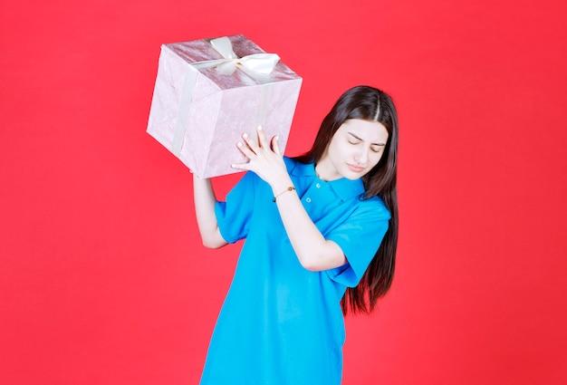 Девушка держит фиолетовую подарочную коробку, обернутую белой лентой.