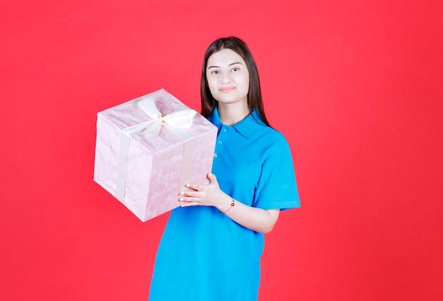 Девушка держит фиолетовую подарочную коробку