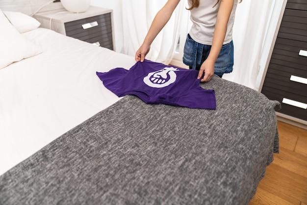 Девушка держит фиолетовую футболку с символом международного феминистского женского дня на кровати в своей комнате