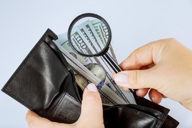 灰色の背景に100ドル札の財布を持っている女の子。虫眼鏡でドル紙幣をチェックします。