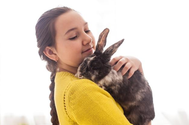 Девушка держит настоящего вислоухого кролика и позирует с ним на камеру