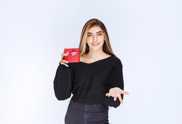 Девушка держит красную подарочную коробку и зовет кого-то подарить. фото высокого качества