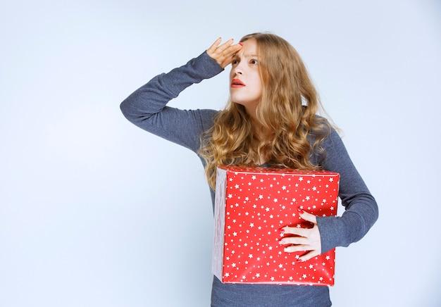 빨간색 선물 상자를 들고 소녀 혼란 스 러 워 보인다.