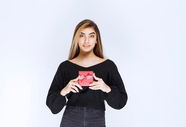 Девушка держит красную подарочную коробку на день святого валентина. фото высокого качества