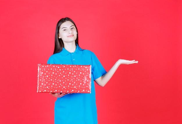 Девушка держит красную подарочную коробку с белыми точками на ней.