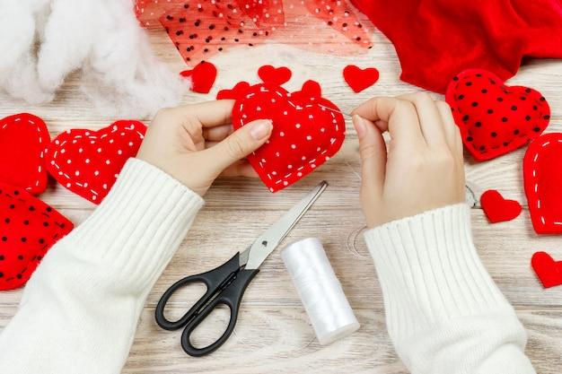 赤いハートを保持している女の子。バレンタインの日グリーティングカード。