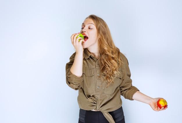 Девушка держит красный персик и кусает зеленое яблоко.