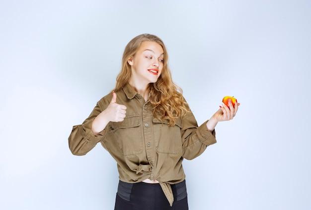 Девушка держит красный персик и показывает знак удовольствия.