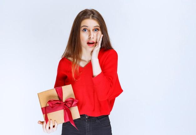 赤いリボンで包まれた段ボールのギフトボックスを持っている女の子は、ストレスと恐怖に見えます。 無料写真