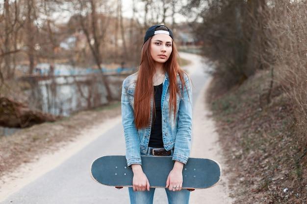 Девушка держит скейтборд на фоне весеннего парка