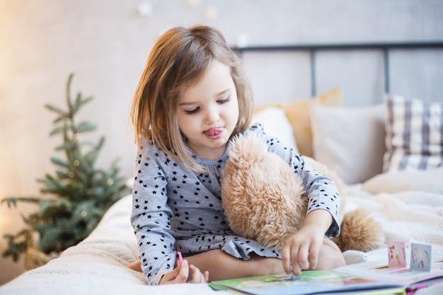 クリスマスにベッドでテディベアを保持している女の子