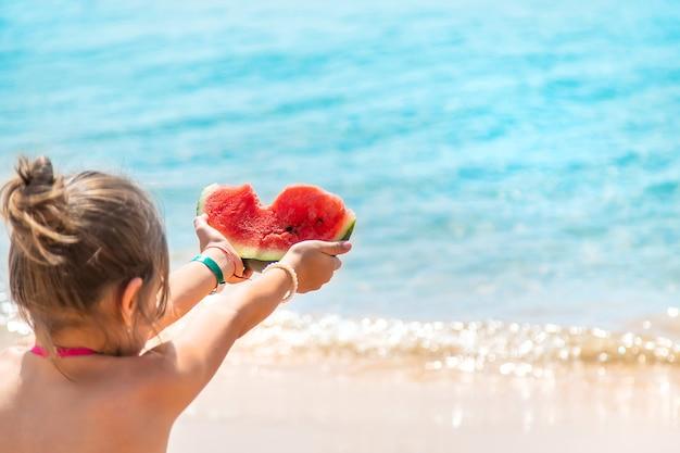 ビーチのトップビューの砂の上にスイカを持っている女の子