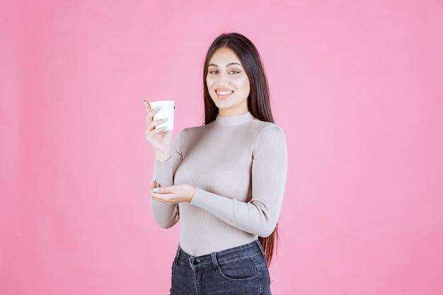 Девушка держит белую одноразовую кофейную чашку, рекламирует ее или нюхает свежий кофе
