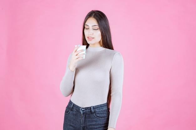 흰색 일회용 커피 컵을 들고 그것을 홍보하거나 신선한 커피 냄새를 맡는 소녀
