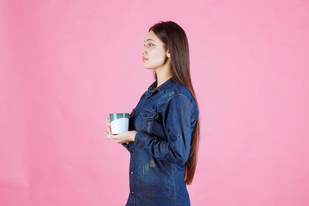 白緑色のコーヒーマグを持って、においがする女の子