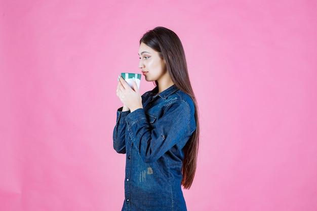 Девушка держит бело-зеленую кофейную кружку и нюхает