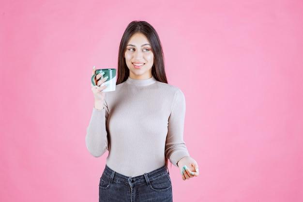 Девушка держит бело-зеленую кофейную кружку и чувствует себя позитивно