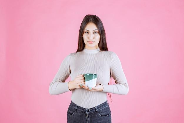 흰색 녹색 커피 잔을 들고 긍정적 인 느낌 소녀