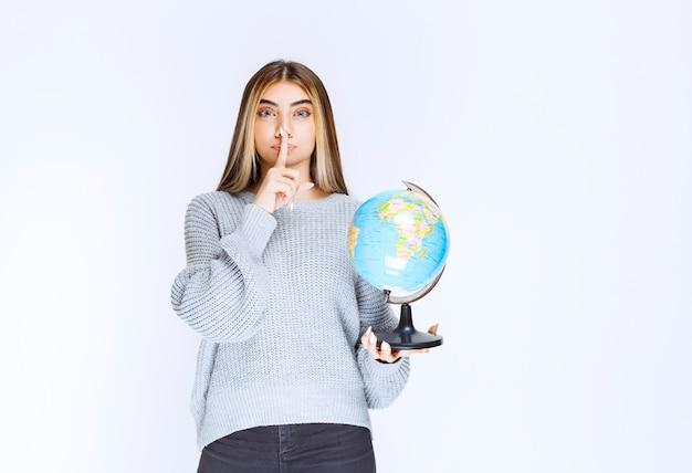 세계 지구본을 들고 침묵을 요구하는 소녀.