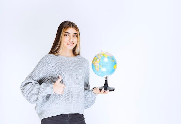 Девушка держит глобус мира и показывает знак удовольствия.