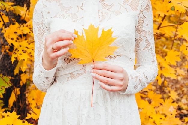 Девушка держит желтый кленовый лист