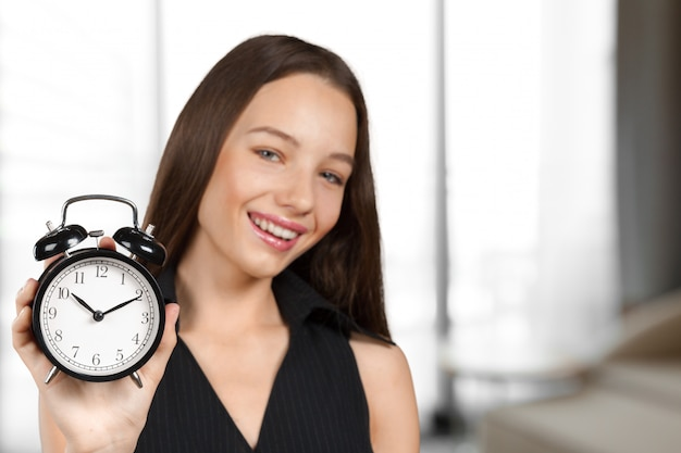 Girl holding alarm clock in hand