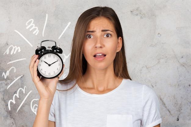 Girl holding alarm clock in hand