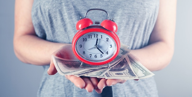 Girl holding an alarm clock and money