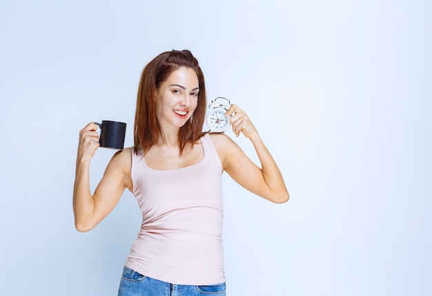Girl holding an alarm clock in one hand and a black coffee mug in another.