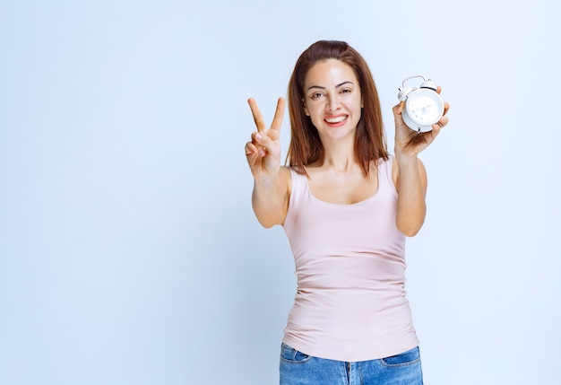 Girl holding an alarm clock and pointing at it.