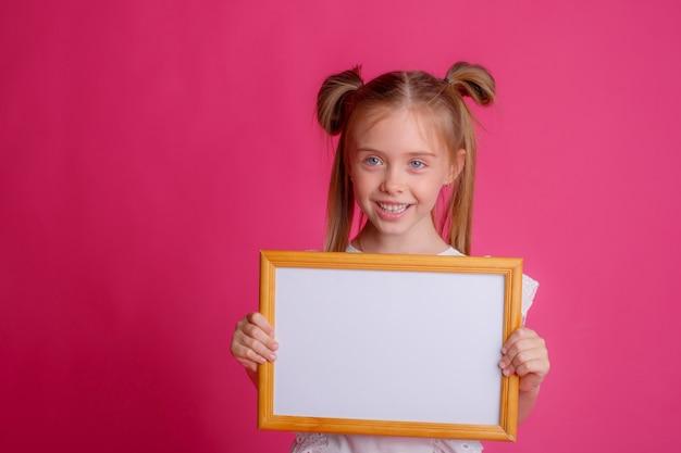 Девушка держит пустую рамку,