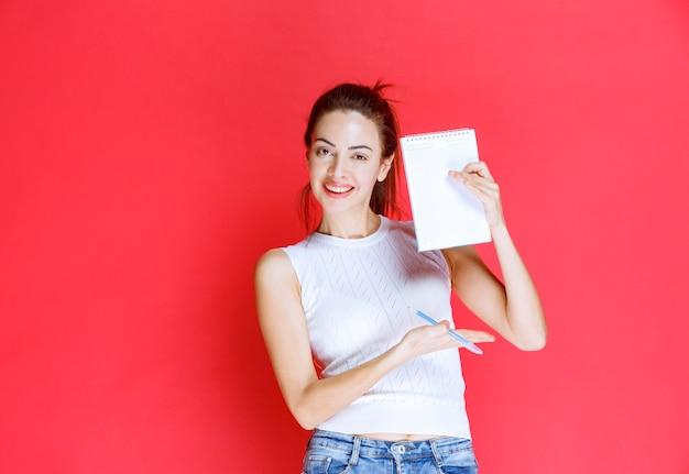 彼女の試験シートを保持し、デモンストレーションする女の子。