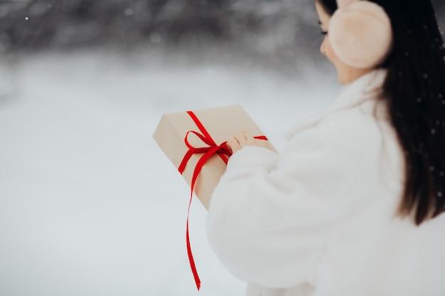 Девушка держит и открывает подарок на день святого валентина.
