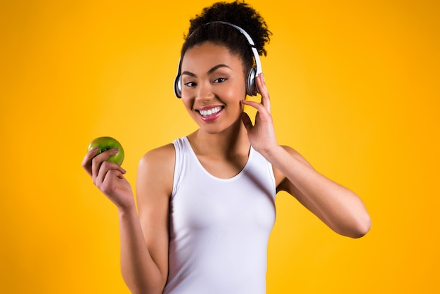 Girl holding an apple in her hand and listening to music