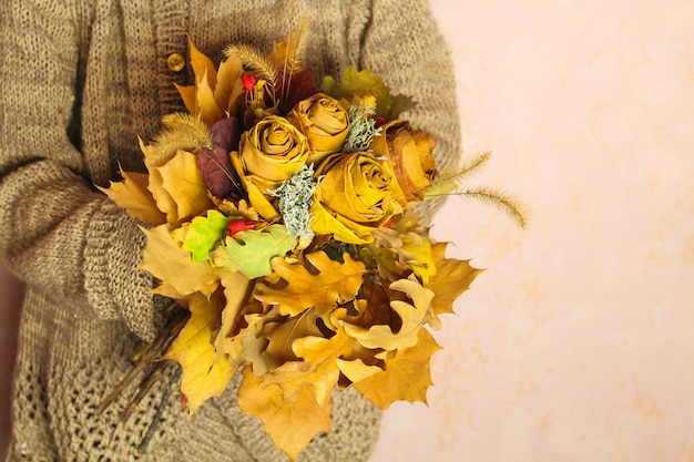 Girl holding autumn bouquet of yellow dry leaves.
