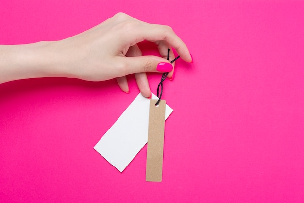 ピンクの紙の背景に値札が付いているバッジを保持している女の子