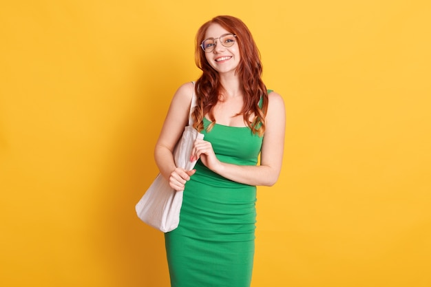 Girl holding bag isolated over yellow space