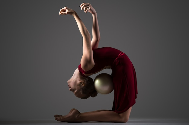 Girl holding a ball with her head and buttlocck