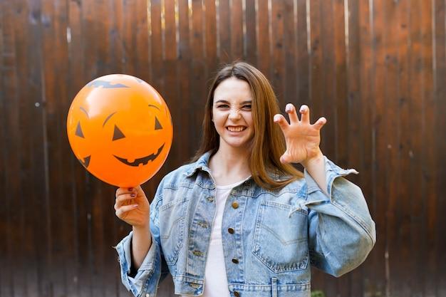Girl holding ballon with pumpkin face