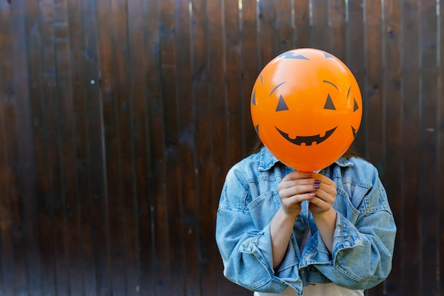 Girl holding ballon with pumpkin face