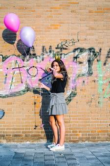 Palloni della tenuta della ragazza davanti alla parete dei graffiti