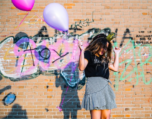 Girl holding balloons in front of graffiti wall